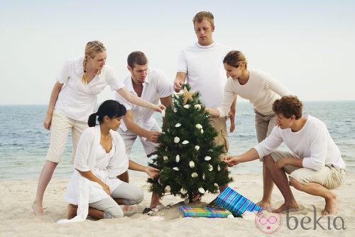 Unos jóvenes decoran un árbol de Navidad en la playa