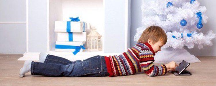Niño viendo una película junto al árbol de Navidad