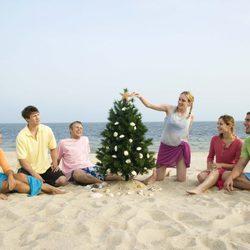 Un grupo de amigos reunidos en torno a un árbol de Navidad en la playa