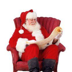 Papá Noel lee la carta de los regalos sentado en un sillón