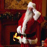 Papá Noel junto a una chimenea tras dejar los regalos de navidad