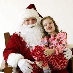 Papá Noel con una niña pidiéndole regalos de navidad