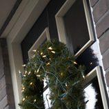 Corona de pino con luces para decorar la casa en navidad